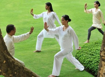 A group of people doing Tai Chi outdoors