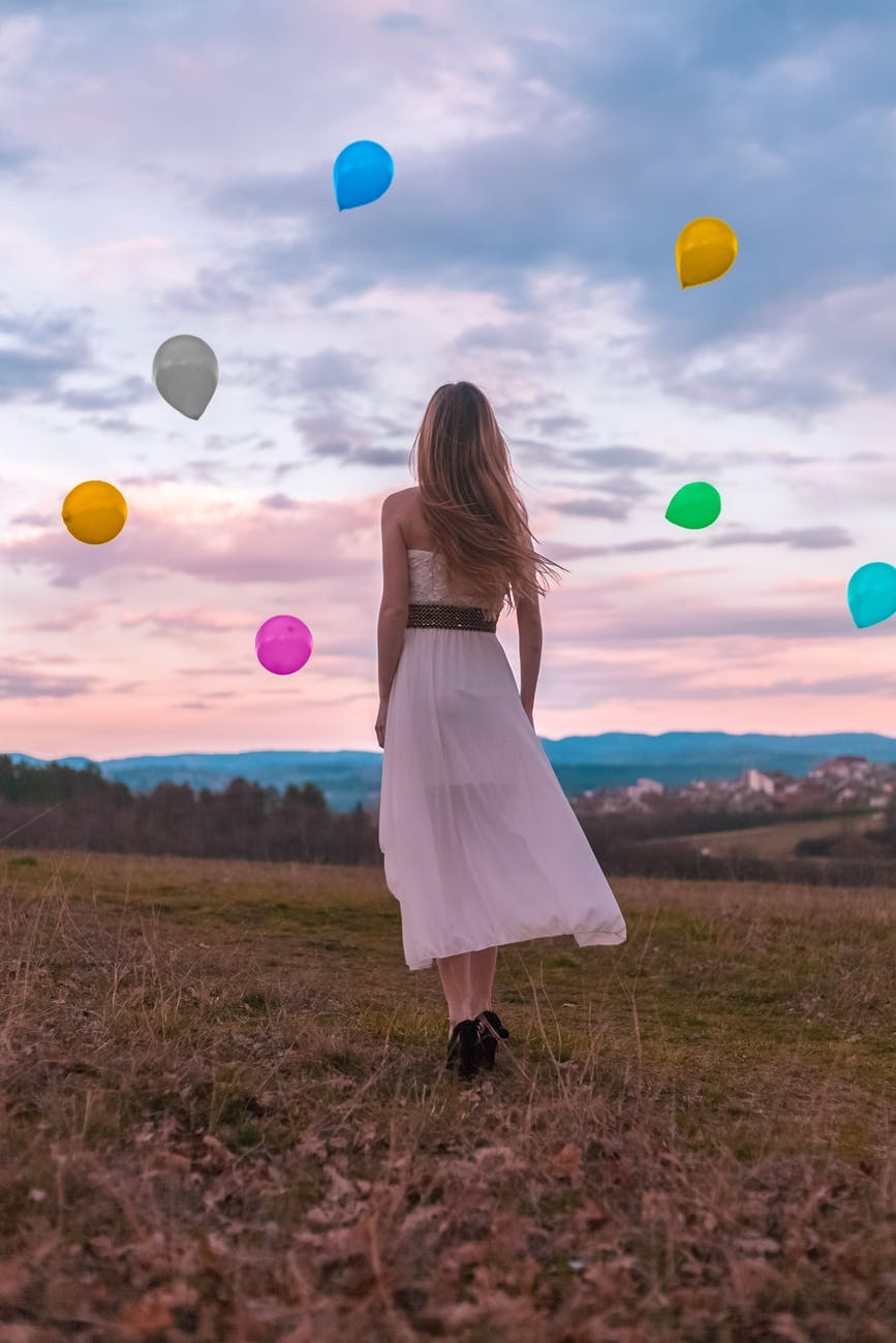 woman in white dress looking at the balloons