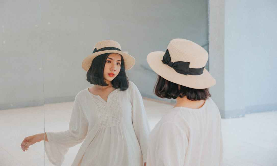 woman wearing white long sleeved dress and beige sun hat